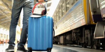Traveler with a blue suitcase is waiting for the train.Hat and headphone placed on the suitcase.