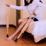 Woman patient using crutches and broken leg for walking in bedroom,Close up