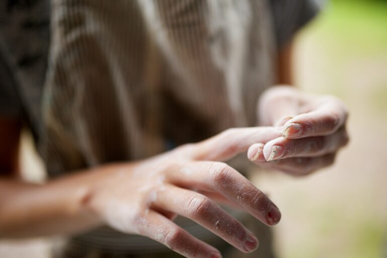 young girl hands cleaning clay from fingers