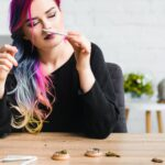 beautiful hipster girl with colorful hair sniffing joint with weed