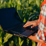 Closeup laptop screen in a male hands. Agronomy standing in a field holding open notebook