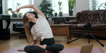 Female yoga coach poses on camera with laptop in apartment