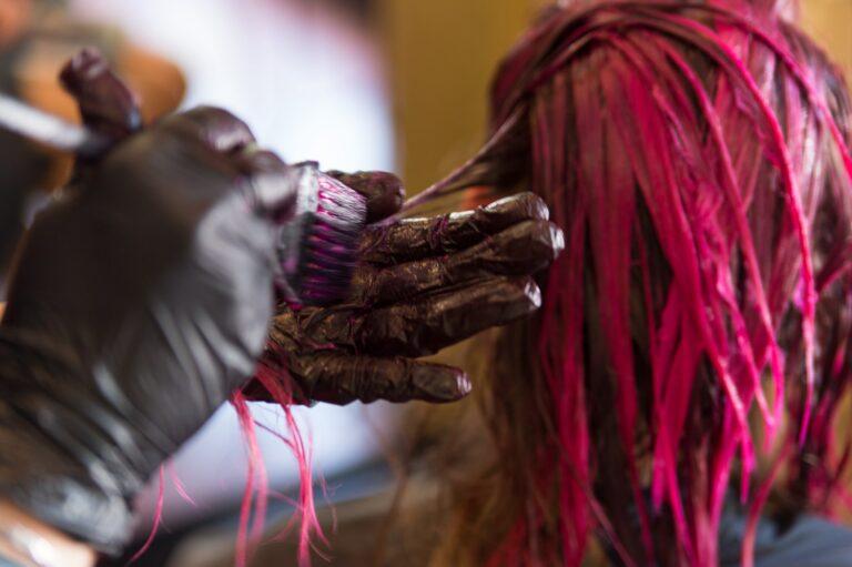Hair dresser dying a woman's blond hair pink.