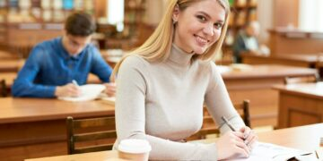 Happy student girl enjoying time in library