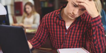 Male student studying at computer