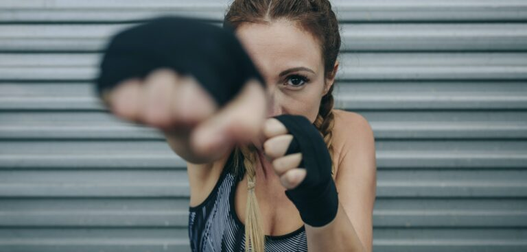 Sportswoman looking at camera and punching