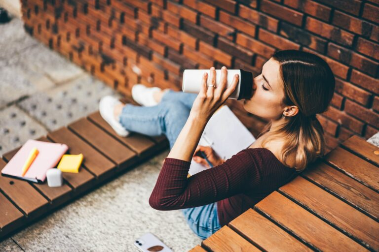 studen writes in paper notebook and drinks coffee from thermocup by brick wall on stone bench.