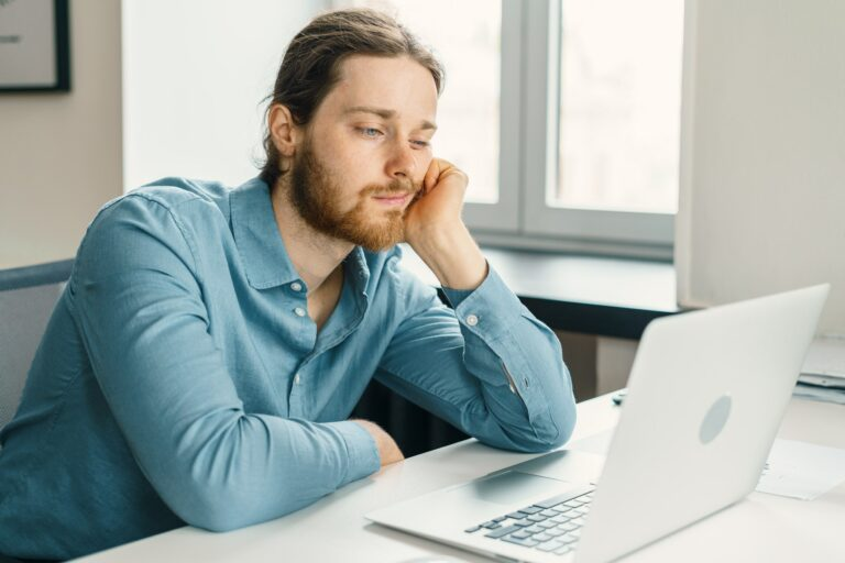 Unhappy male office worker feeling bored at work
