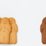 white gingerbread men and a sad black gingerbread man in kids racism and racial segregation concept