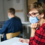 Young student with face mask at desk at college or university, coronavirus concept.