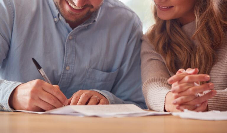 Close Up Of Smiling Couple Signing Financial Document At Home