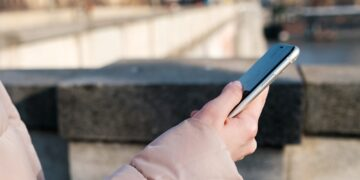 Close up woman hands holding a smartphone. Young girl uses messenger, free wi fi or internet