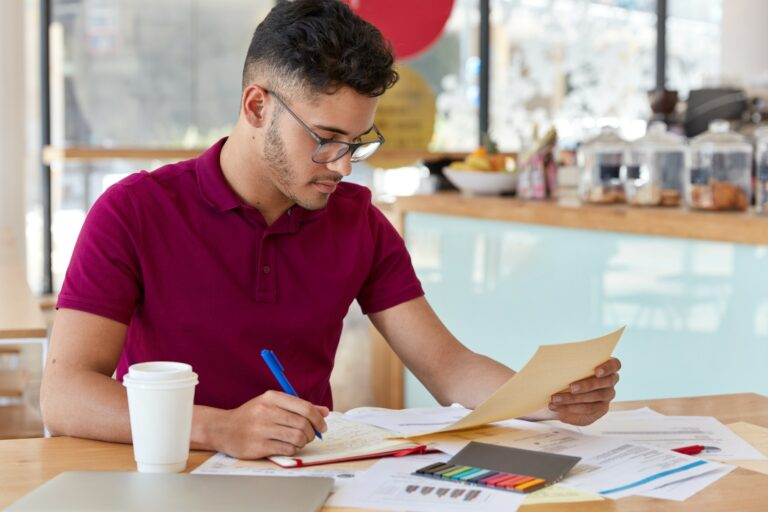 Image of busy unshaven copy writer or college student dressed in casual clothing, makes notes in not