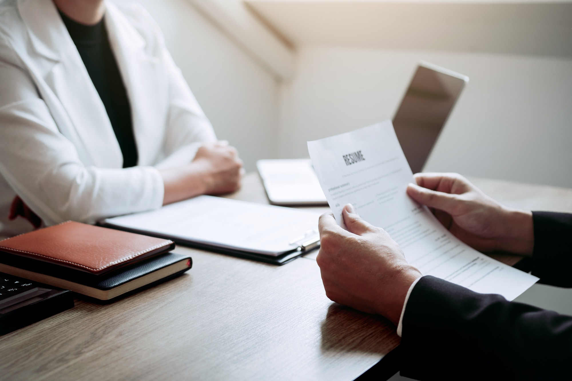 Job applicants are holding a resume document in the job interview room, job interview concept.