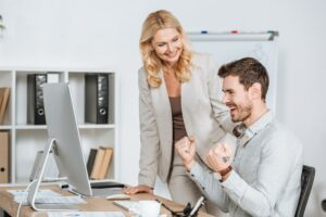 smiling female mentor looking at happy young businessman working with desktop computer in office