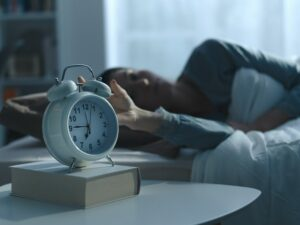 Woman waking up in the morning and alarm clock